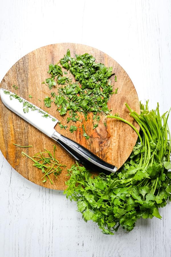 Chopped cilantro on round cutting board.