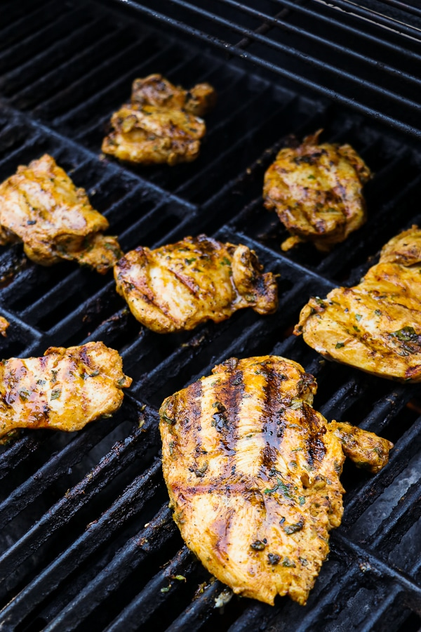Cilantro lime chicken breasts and thighs on grill grates.