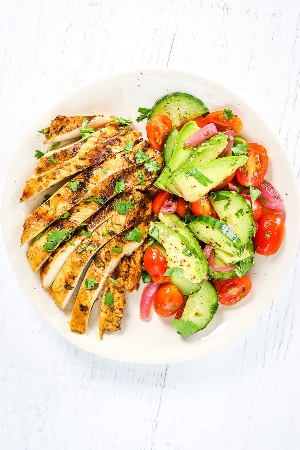 Sliced cilantro lime chicken with avocado cucumber salad on the side.