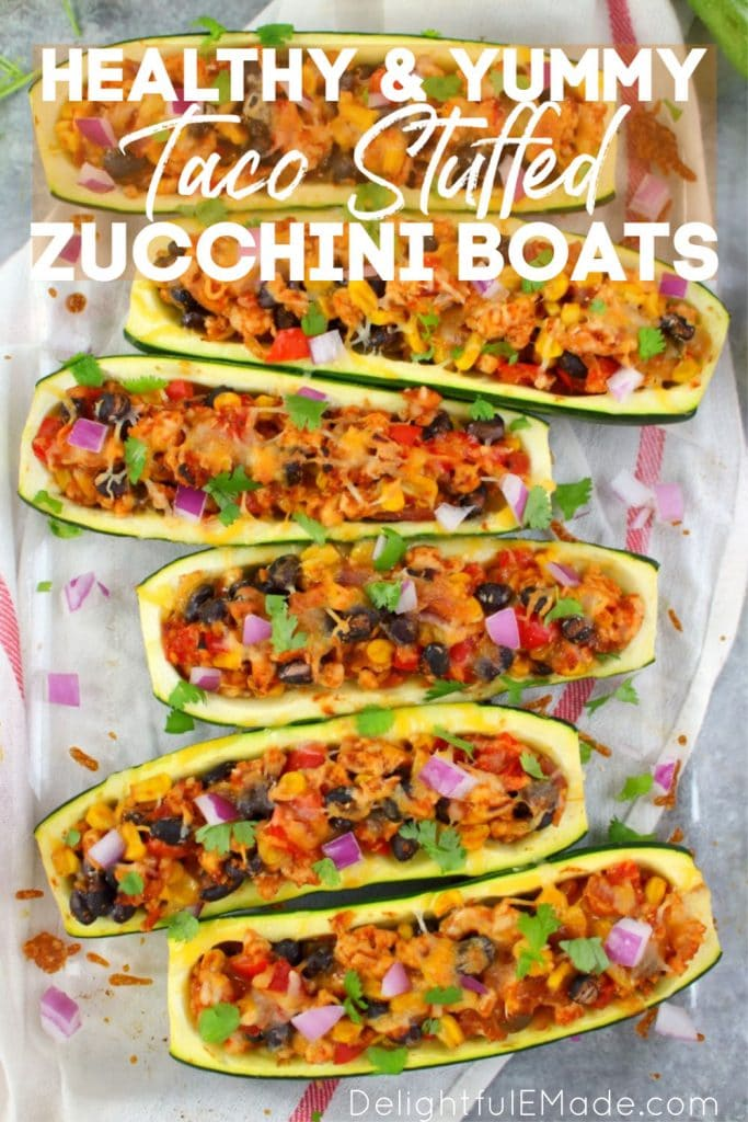 Pan of horizontally sliced stuffed zucchini boats with ground turkey taco filling and melted cheese.