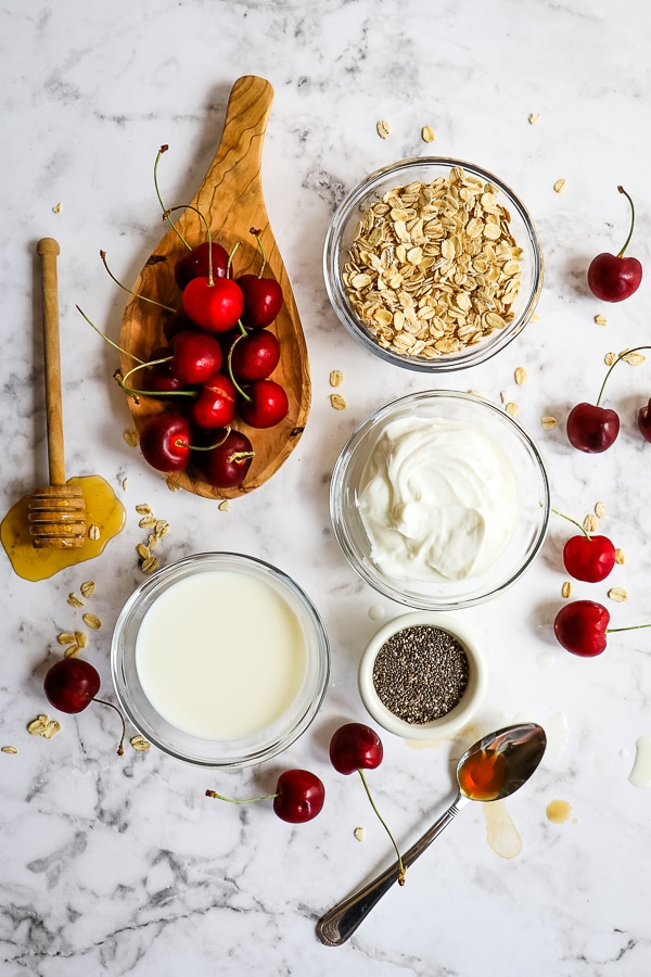 Ingredients for cherry overnight oats; whole, fresh cherries, rolled oats, Greek yogurt, milk, chia seeds, vanilla extract and honey.