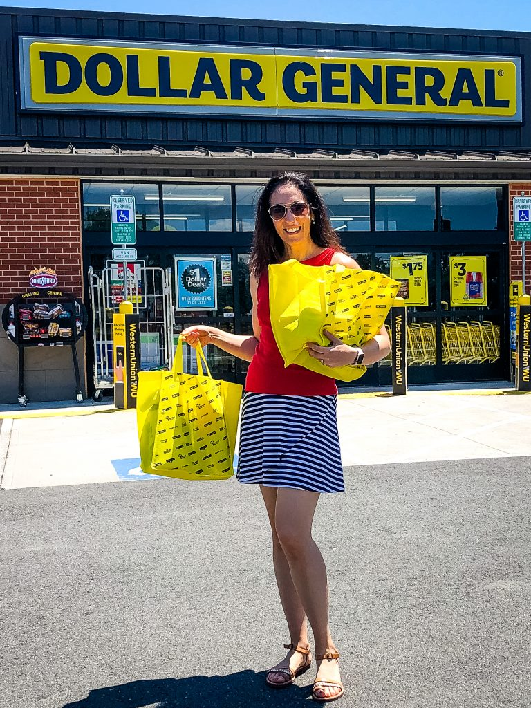 Erin in front of Dollar General store with yellow bags of school supplies.