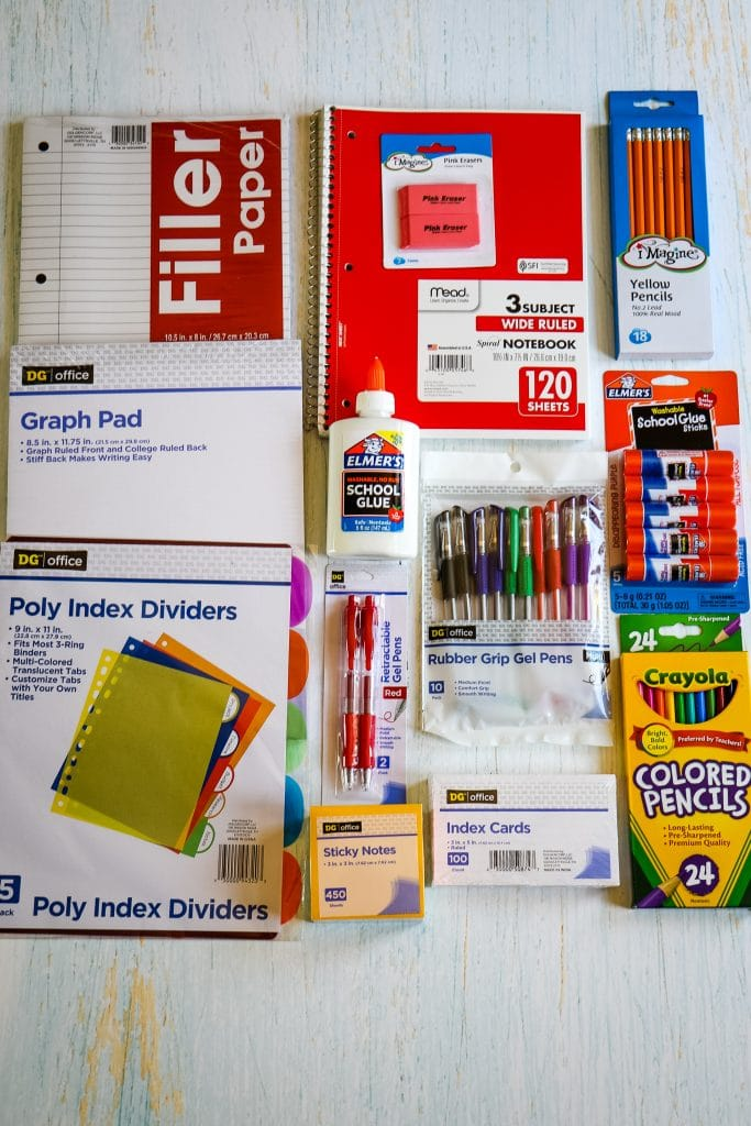 White table top with an assortment of school supplies.