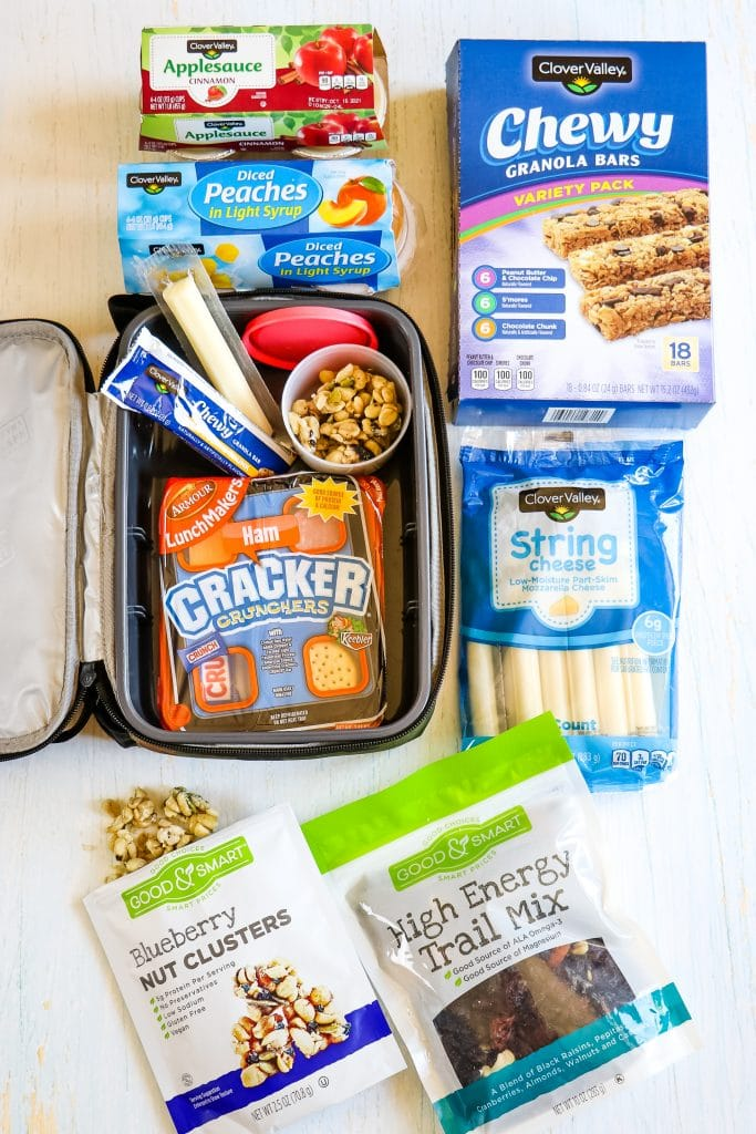 White tabletop with an assortment of snacks and lunchbox items ready for packing inside lunchbox.