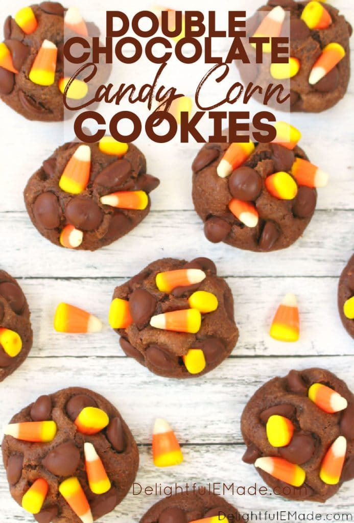 Double chocolate candy corn cookies, on white surface garnished with candy corns.