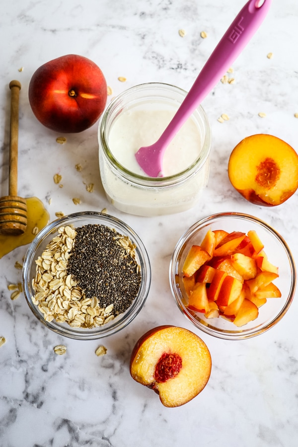 Mixing together the peach overnight oats, cup of oats and seeds, peach chunks and yogurt.