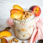 Peach overnight oats topped with walnuts and peach slices.