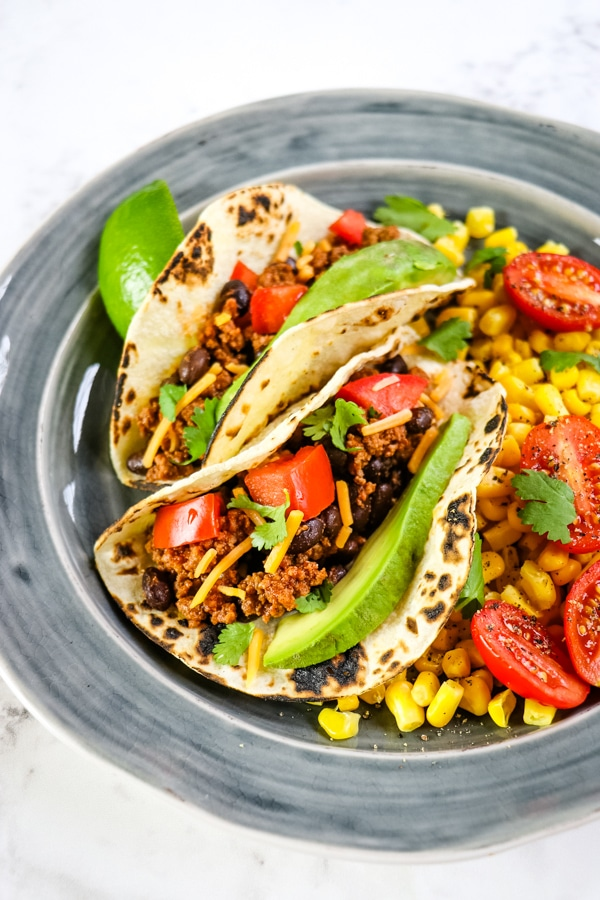 Two ground beef tacos on a plate with corn and tomato side. Topped with cilantro and avocado slices.