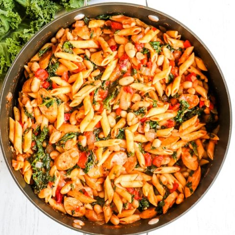 Healthy chicken sausage pasta with kale, white beans, roasted red peppers in a large skillet.