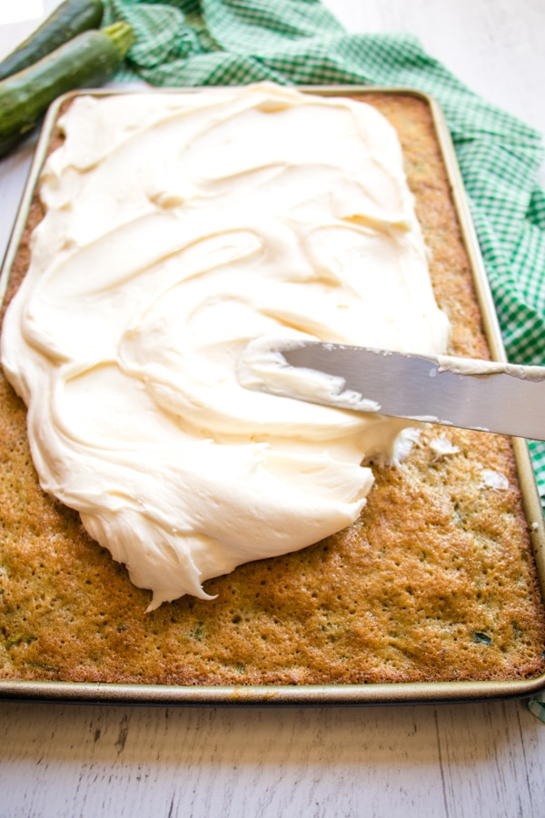 zucchini cake being frosted with cream cheese frosting