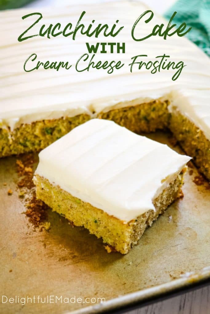square slice of zucchini cake with cream cheese frosting in sheet pan.