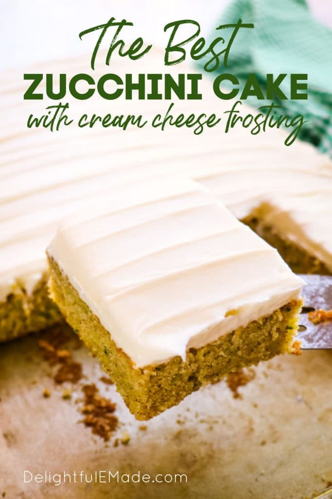 slice of zucchini cake with cream cheese frosting on spatula lifted from pan.