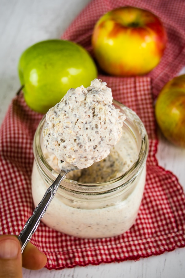 Jar of apple cinnamon overnight oats with spoonful of oats