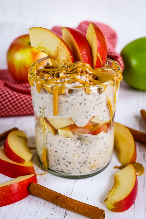 Jar of apple cinnamon overnight oats topped with apple slices and peanut butter.