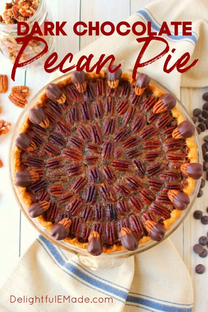 Dark chocolate pecan pie recipe in pie plate garnished with chocolate chips and pecans.