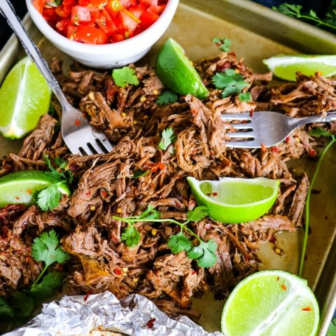 Mexican shredded beef barbacoa on sheetpan with limes, avocados and tortillas.