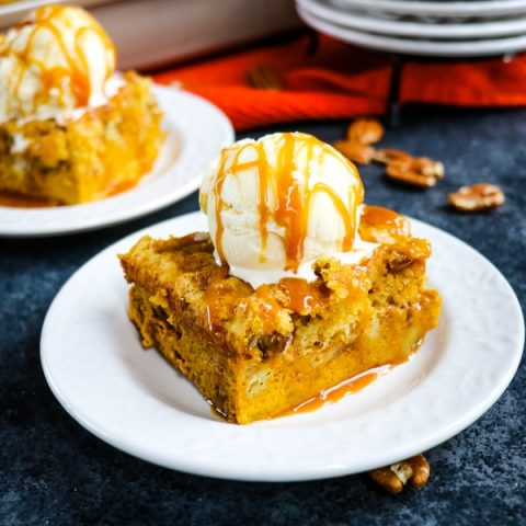 slice of pumpkin dump cake topped with vanilla ice cream and caramel drizzle.