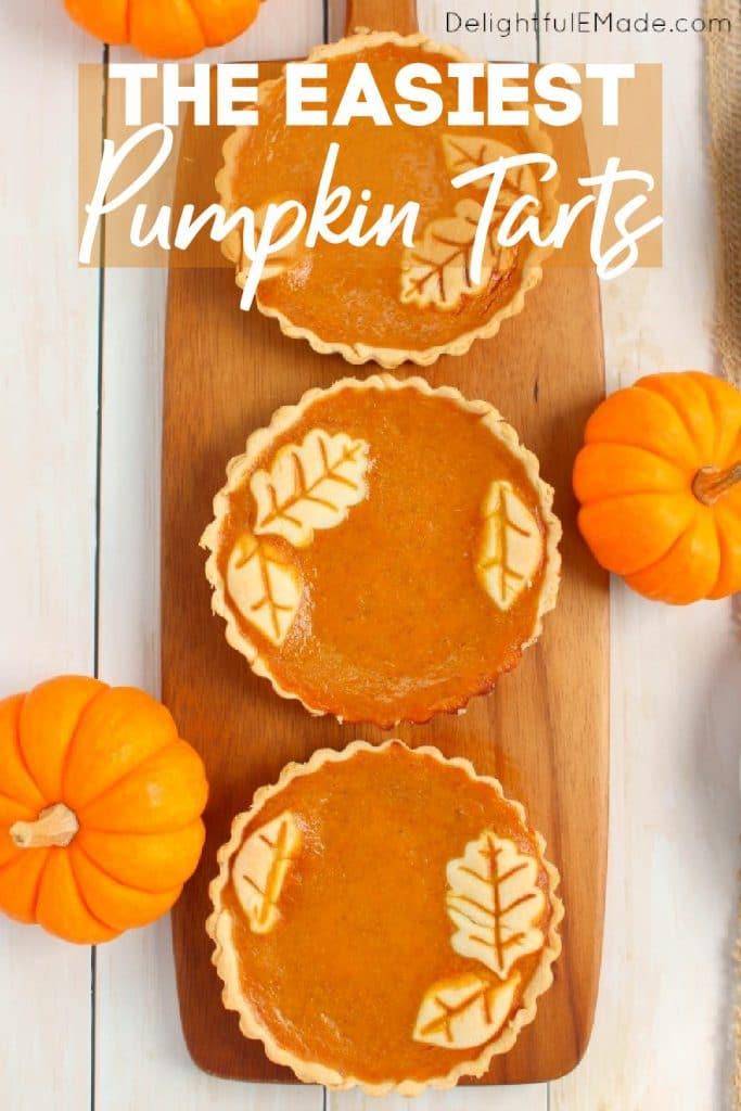 Pumpkin tarts on board garnished with mini pumpkins.