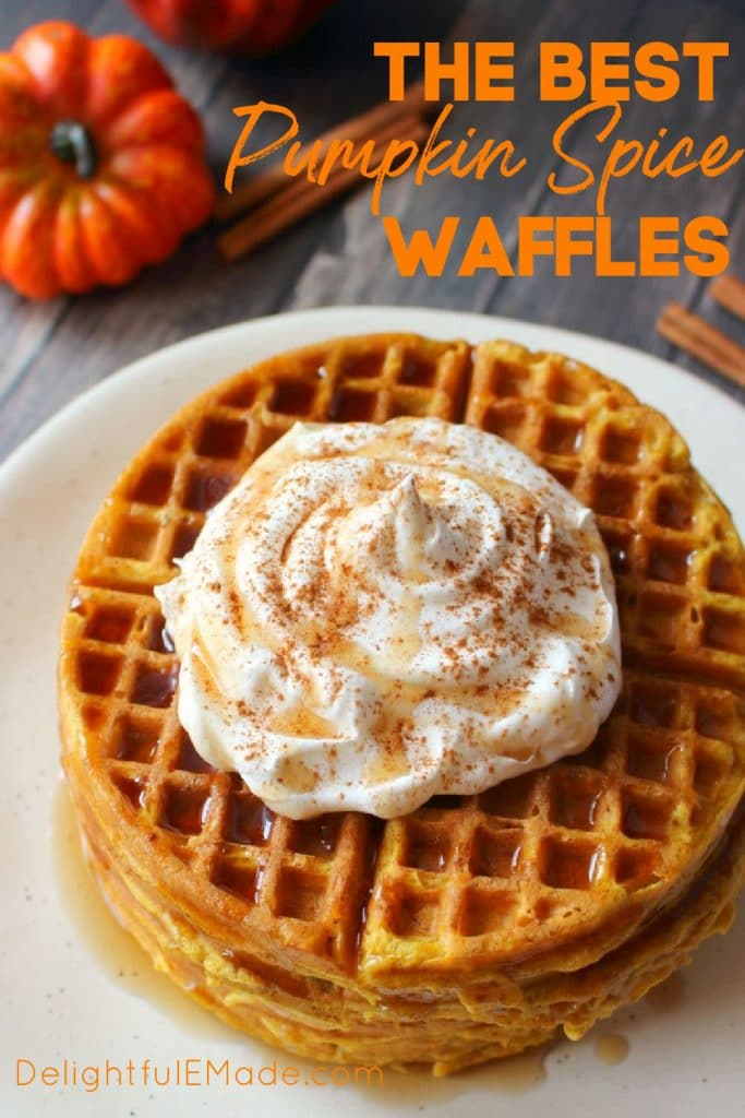 Pumpkin spice waffles topped with whipped cream and syrup.