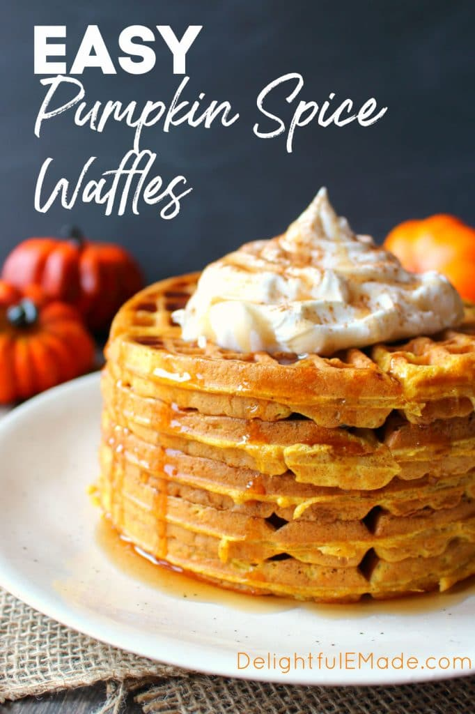 Stack of pumpkin spice waffles topped with whipped cream.