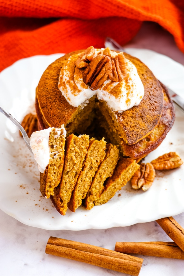 Stack of pumpkin spice pancakes with bite take out.