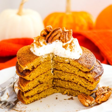 Healthy pumpkin pancakes, stacked on a plate with pecans and yogurt on top.