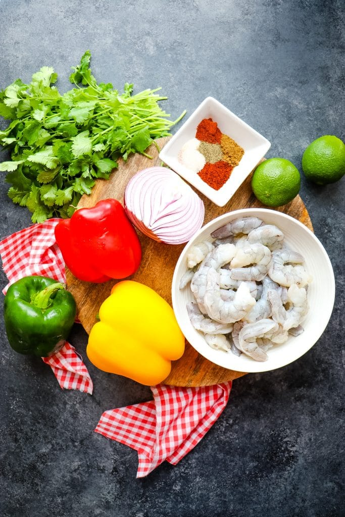 Ingredients on board for sheet pan shrimp fajitas.