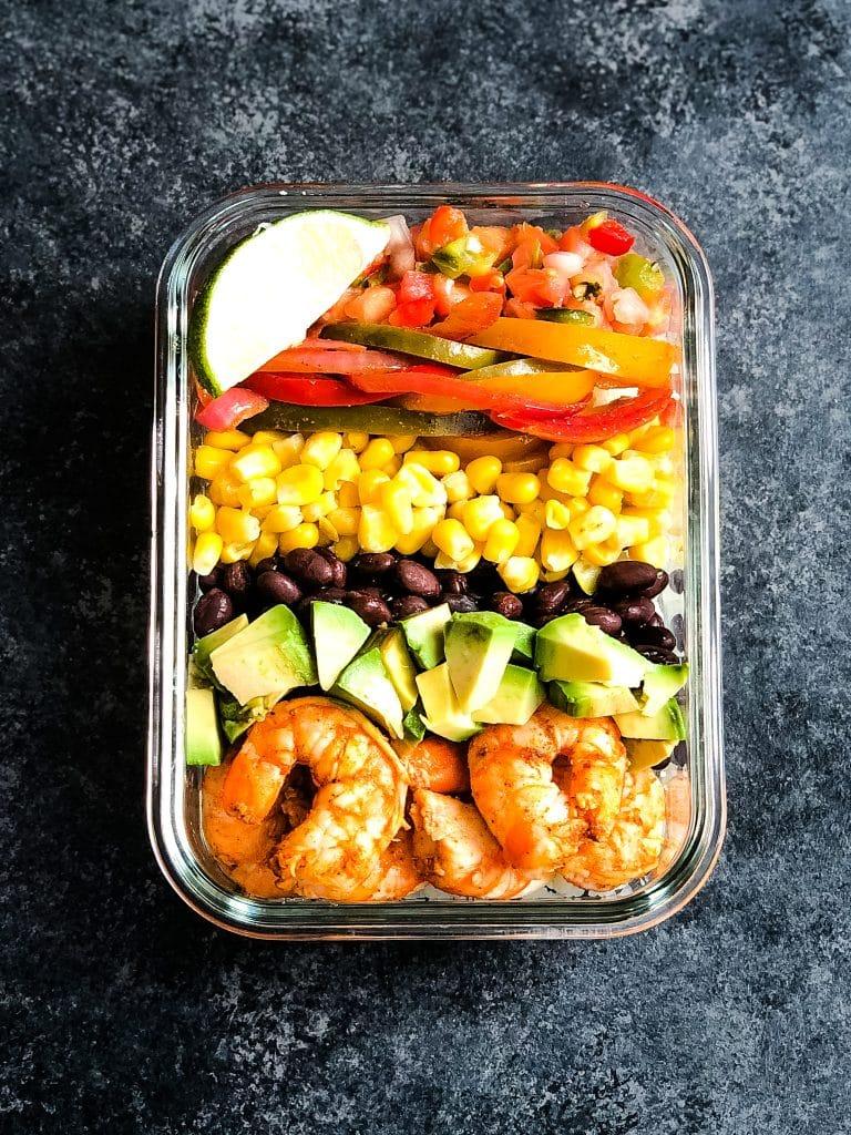 Sheet pan shrimp fajitas in a meal prep container.