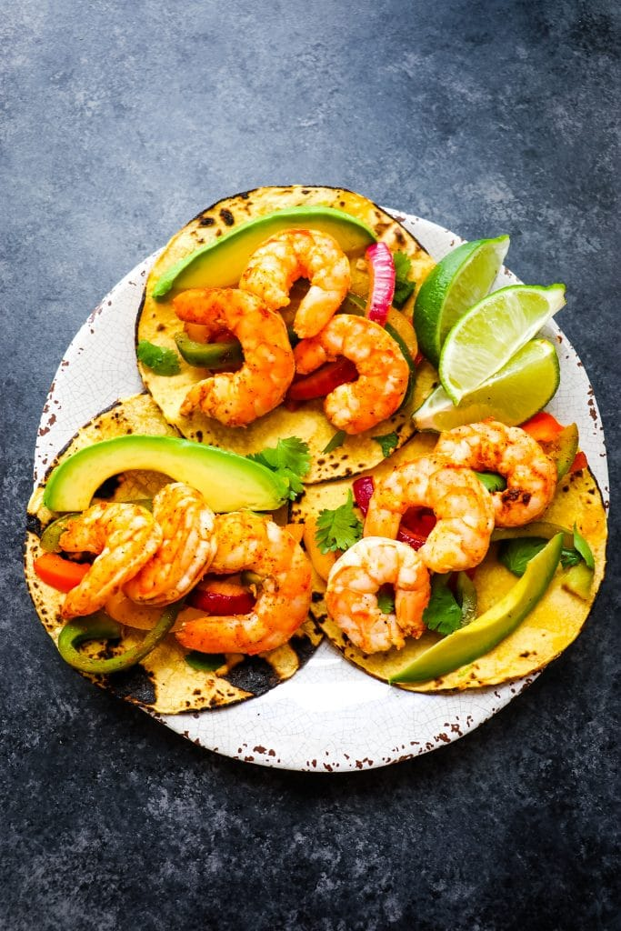 Plate of shrimp fajita recipe topped with avocados, cilantro and lime wedges.