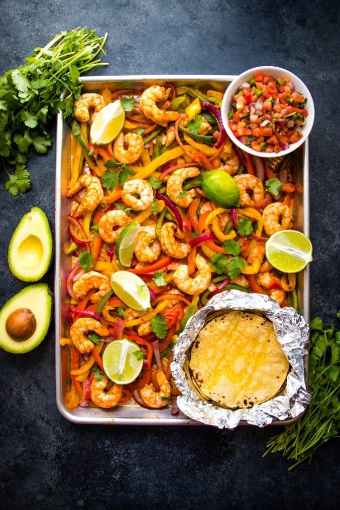 Baked shrimp fajitas recipe on sheet pan with tortillas.