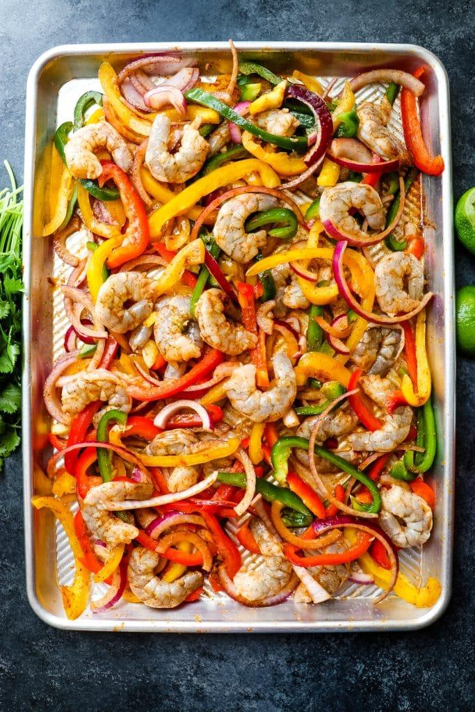All ingredients tossed together for sheet pan shrimp fajitas.