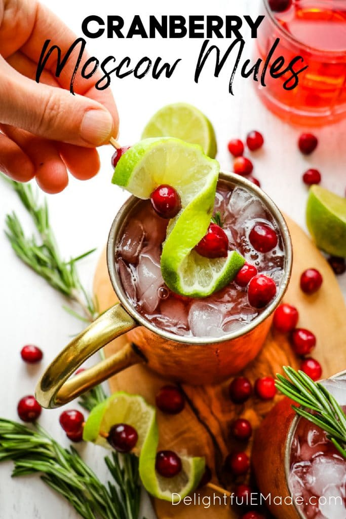 Garnish being placed on top of Cranberry Moscow Mules.