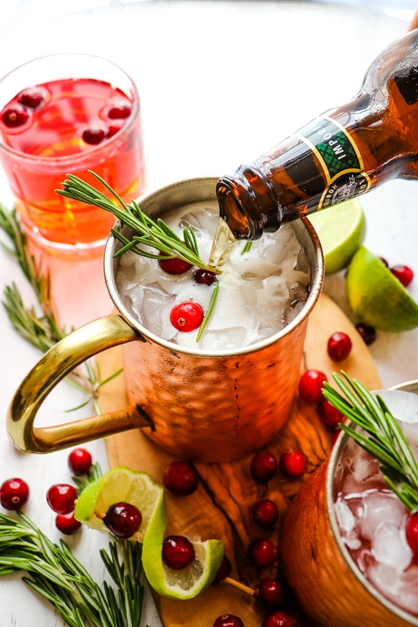 Pouring ginger beer into Cranberry moscow mule.