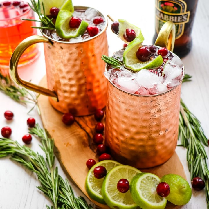 Cranberry Moscow mules topped with limes, rosemary and cranberries. Christmas moscow mules