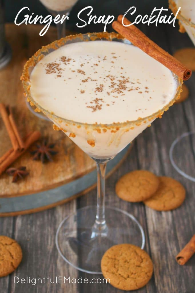 Single martini glass of ginger snap cocktail garnished with cinnamon stick and cookies.