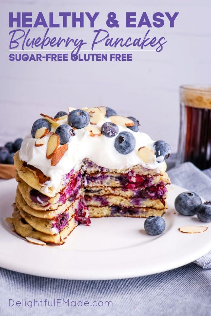 Healthy blueberry pancakes, blueberry oatmeal pancakes topped with yogurt, blueberries and sliced almonds.