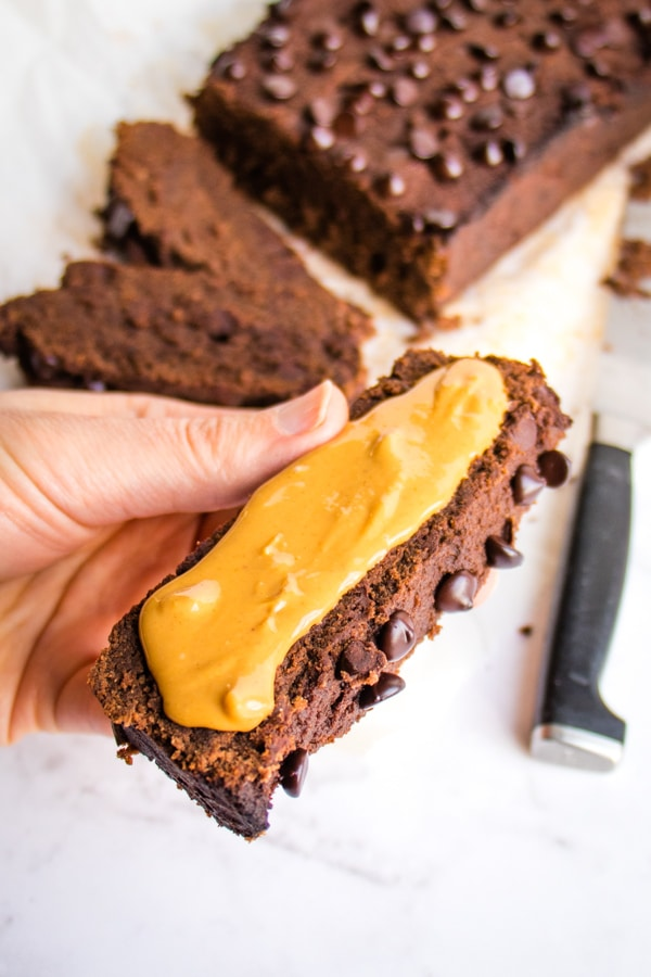 Healthy chocolate banana bread slice topped with peanut butter.