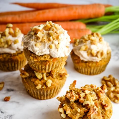 Carrot cake muffins recipe topped with walnuts and cream cheese frosting.