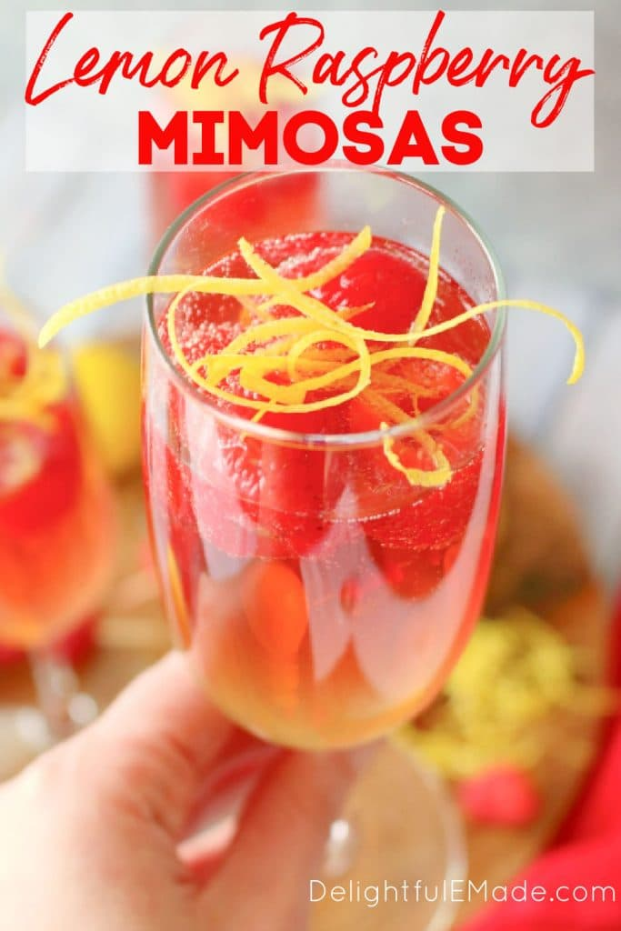 Lemon raspberry mimosa in a champagne glass topped with raspberries and lemon zest.