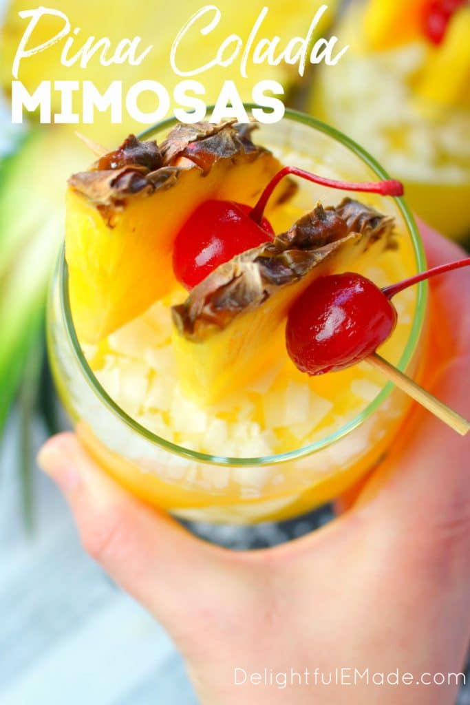 Pina colada champagne punch, champagne punch recipe, glass held with pineapple cherry garnish.