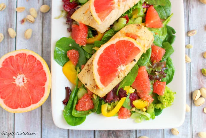 Grapefruit spinach salad recipe with mahi mahi, entrée salad on a white plate.