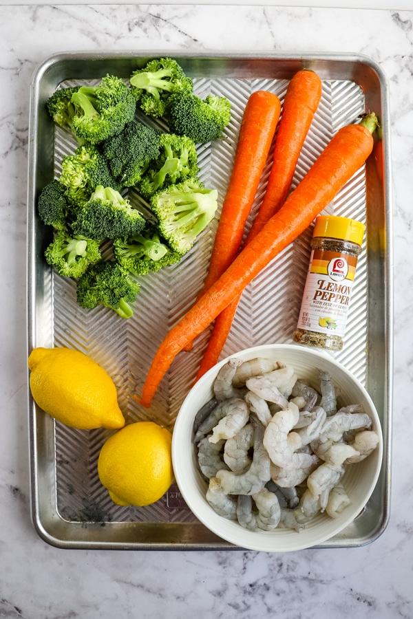 Ingredients for lemon pepper shrimp with vegetables on sheet pan.