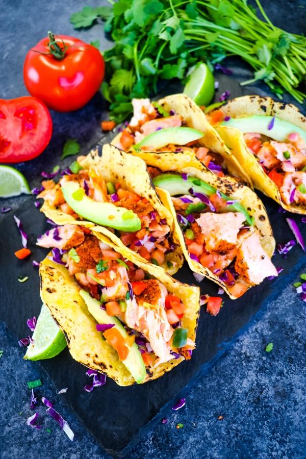 Salmon Tacos recipe on board with cilantro, avocado salsa.