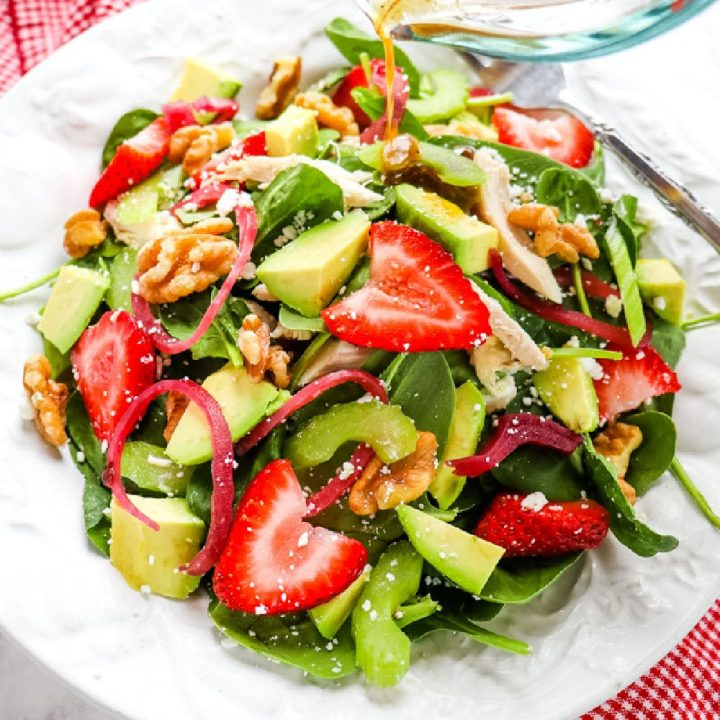 Strawberry spinach salad recipe with avocado, chicken and walnuts.