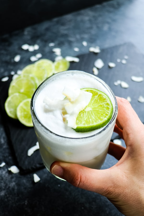 Coconut margarita recipe on the rocks with lime slice and coconut flakes.