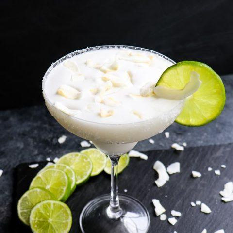 Coconut margarita recipe, with lime slices and coconut flakes.