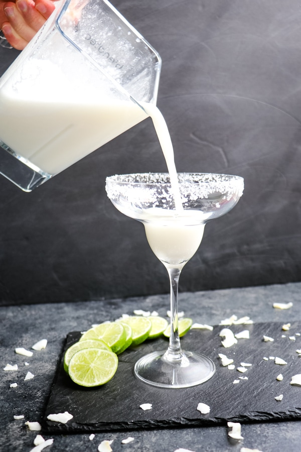 Pouring blended coconut margarita into ups glass.