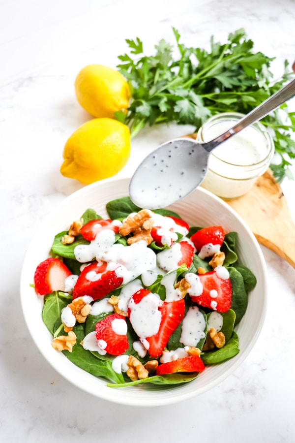 Creamy poppy seed dressing recipe, spooned over strawberry salad.