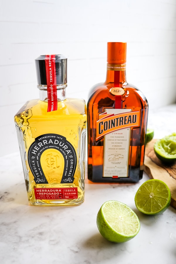 Herradurra tequila and cointreau liqueur bottles with lime halves.