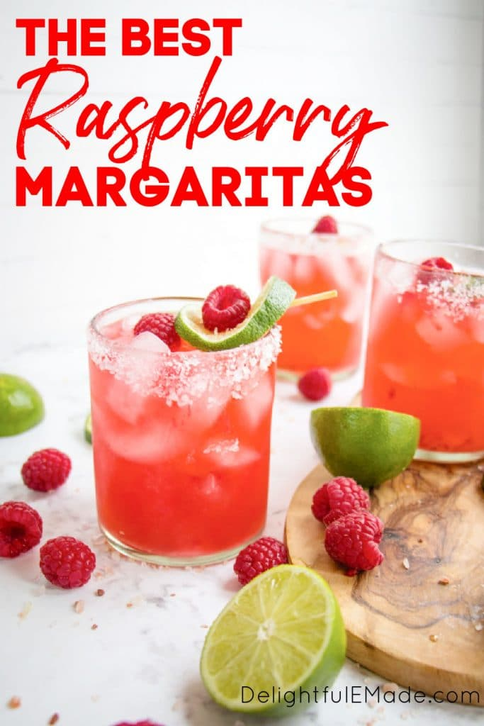 Raspberry margarita on the rocks with fresh raspberries and lime slices.
